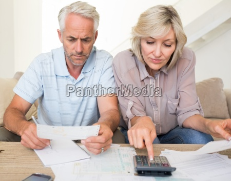 concentrated mature couple with bills and