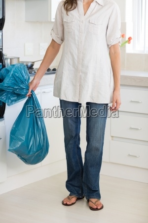 low section of woman carrying garbage
