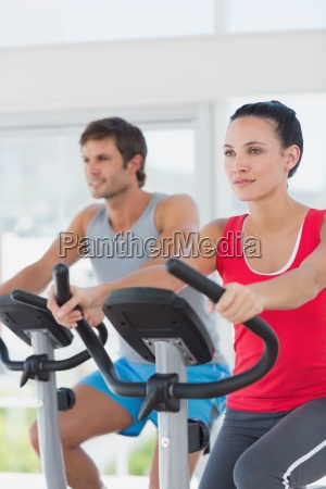 determined couple working out at spinning