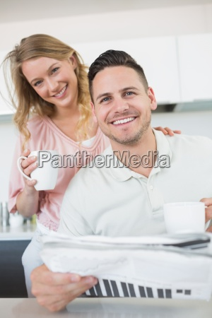 couple with coffee mugs and newspaper
