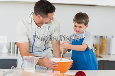 father and son making cookies at