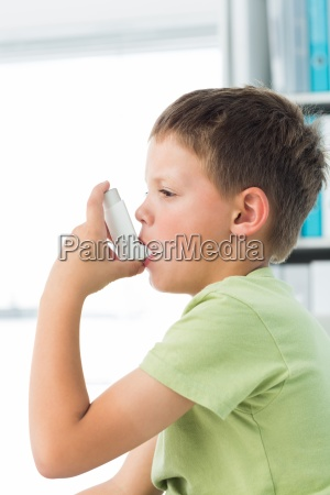 boy using asthma inhaler in hospital
