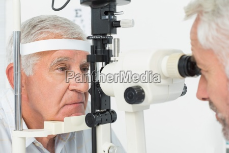 optometrist doing sight testing for senior