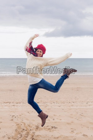 woman in stylish warm clothing jumping