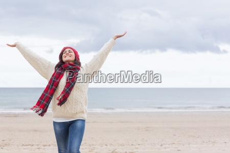 woman in warm clothing stretching arms