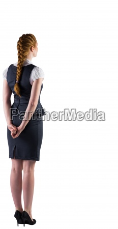 redhead businesswoman standing with hands behind