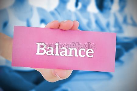 woman holding pink card saying balance