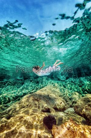 woman swimming near rock