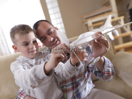 father and son assembling airplane toy