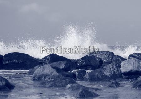 black rocks protecting coast against crashing