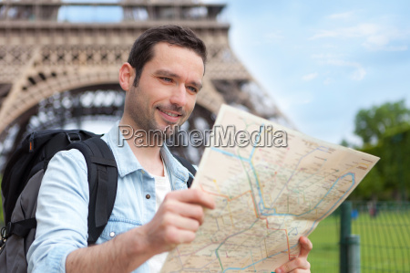 young attractive tourist reading map in