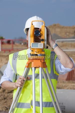 surveyor looking through theodolite at construction