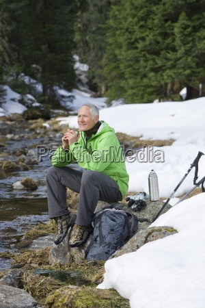 smiling man with backpack and ski
