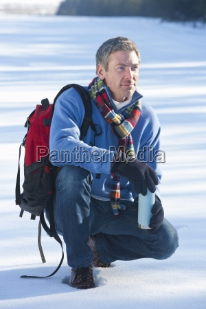 man crouching in snow with backpack
