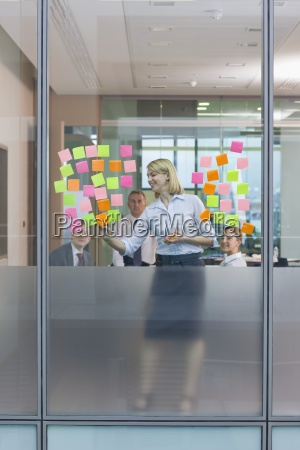 view of businesswoman placing adhesive notes