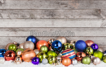 assorted christmas balls decorations on snow