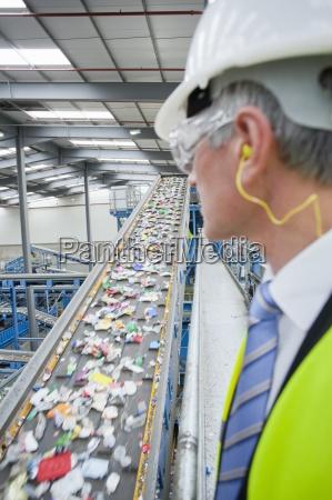 businessman watching plastic on conveyor belt