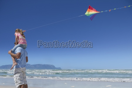 father carrying daughter with kite on