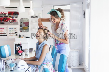 hairdresser placing curlers in womans hair
