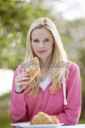 eine junge frau isst ein croissant