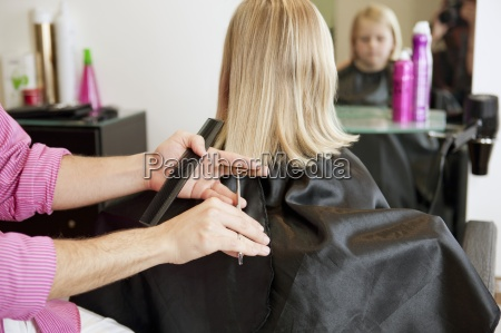 a male hairdresser cutting a young