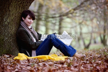 a woman sitting under a tree
