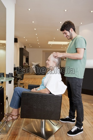 a male hairdresser applying product to