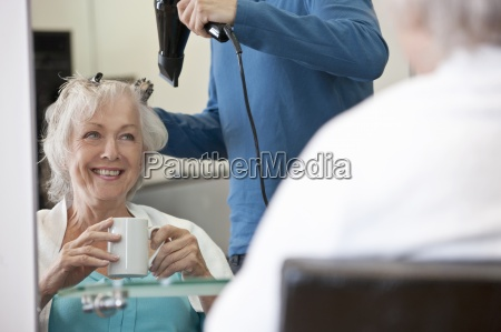a senior woman drinking a hot