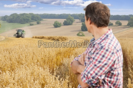 farmer watching tractor and trailer in