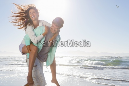 man piggybacking enthusiastic woman on sunny