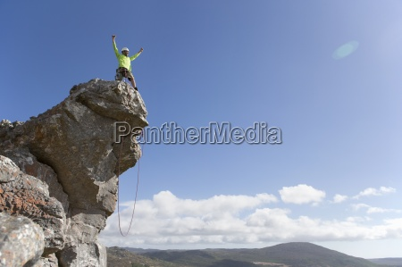 male rock climber standing with arms