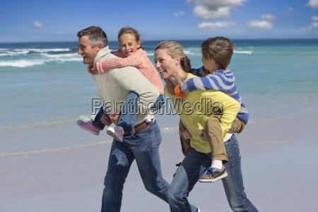 happy parents piggybacking on sunny beach