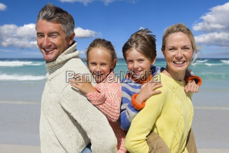 portrait of smiling parents piggybacking children