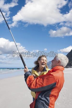 enthusiastic senior couple fishing on sunny