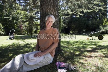 mature man sitting in garden against