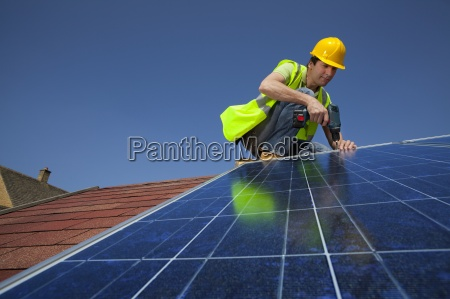 engineer installing solar panel on rooftop