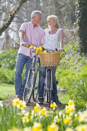 smiling senior couple with bicycles face