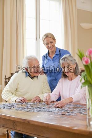 smiling home caregiver watching senior senior