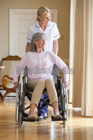 smiling home caregiver pushing senior woman