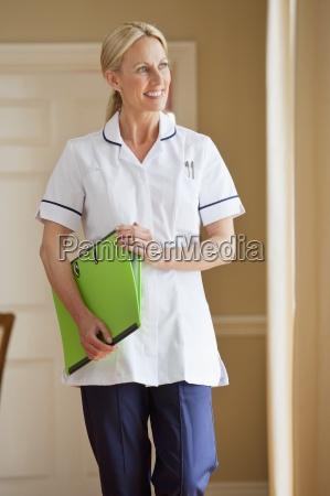smiling home caregiver holding medical record