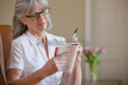 senior woman holding sudoku book and