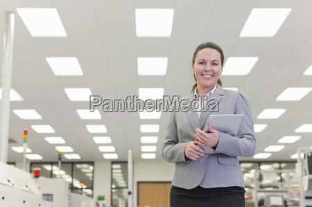 portrait of smiling businesswoman holding digital