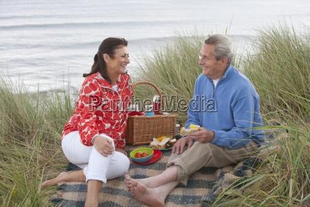 mature couple enjoying picnic in sand