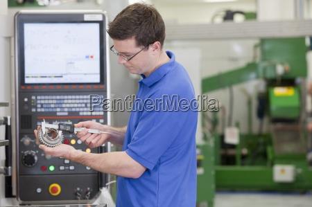 technician measuring gear wheel with vernier