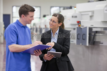 smiling technician and businesswoman with clipboard