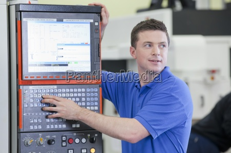technician controlling lathe cutting machine in