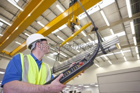technician operating hoist with raw aluminum
