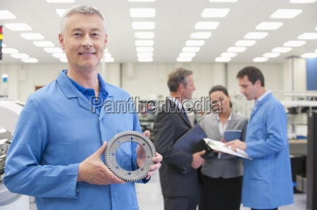 portrait of smiling engineer with machine