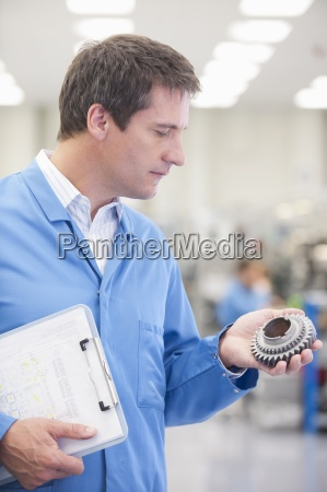 engineer with clipboard examining machine part