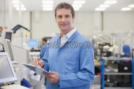 portrait, of, smiling, engineer, with, clipboard - 12915796